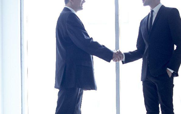 窓際で握手する男性2人